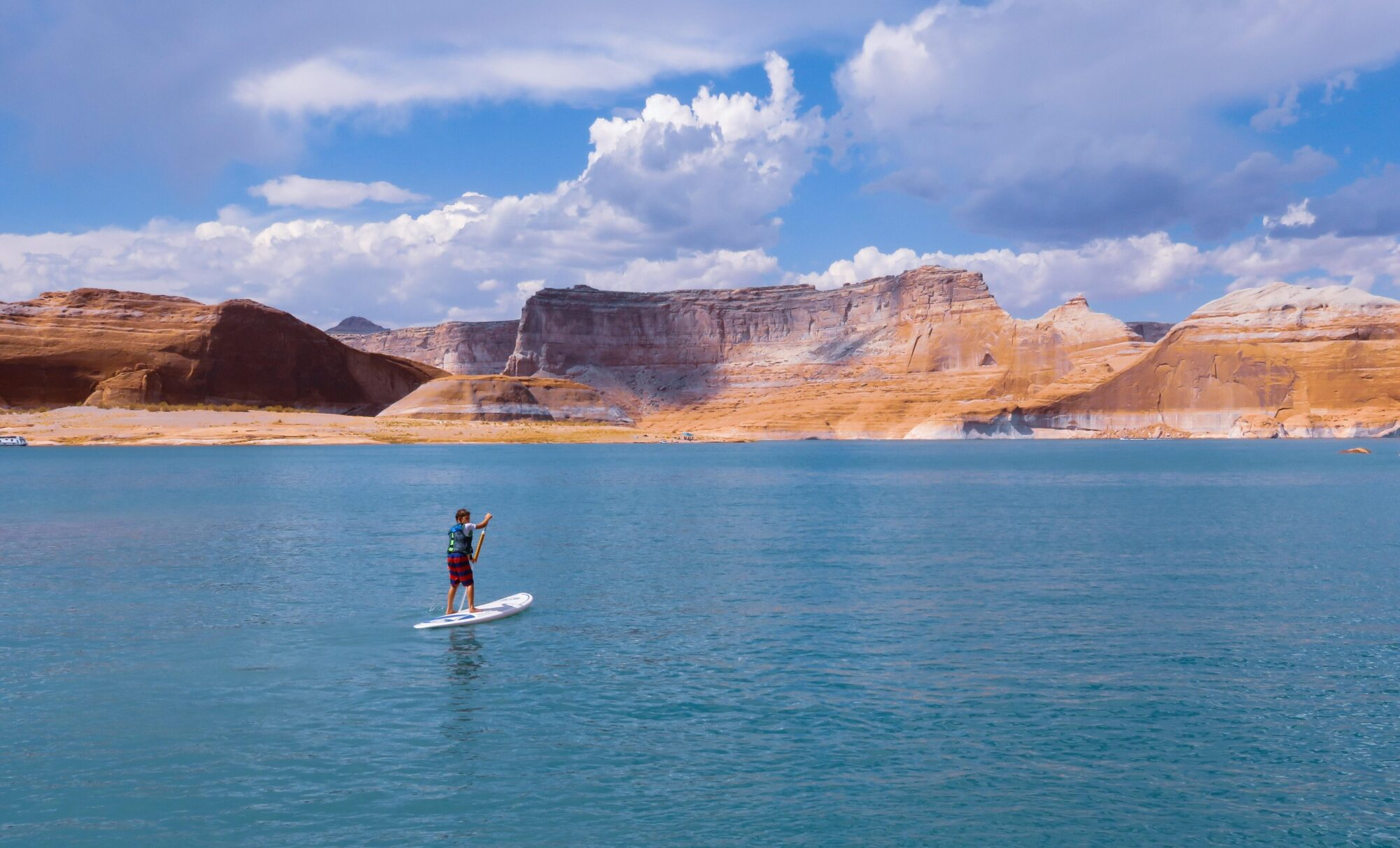 A young man paddleboarding on Lake powell with high cliffs on the far shore