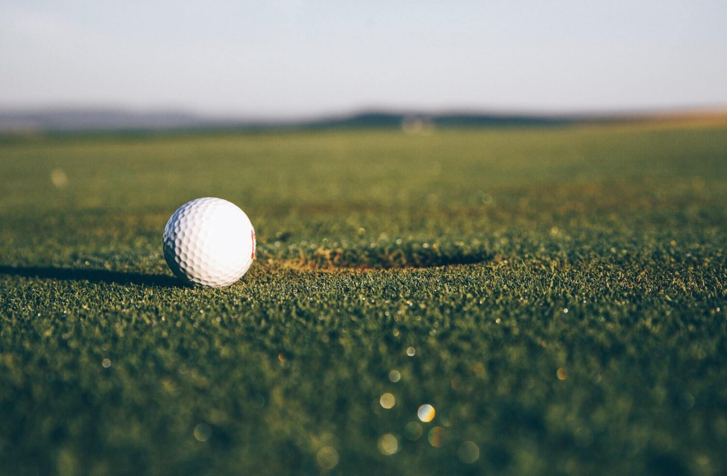 a gold ball sitting very close to the hole