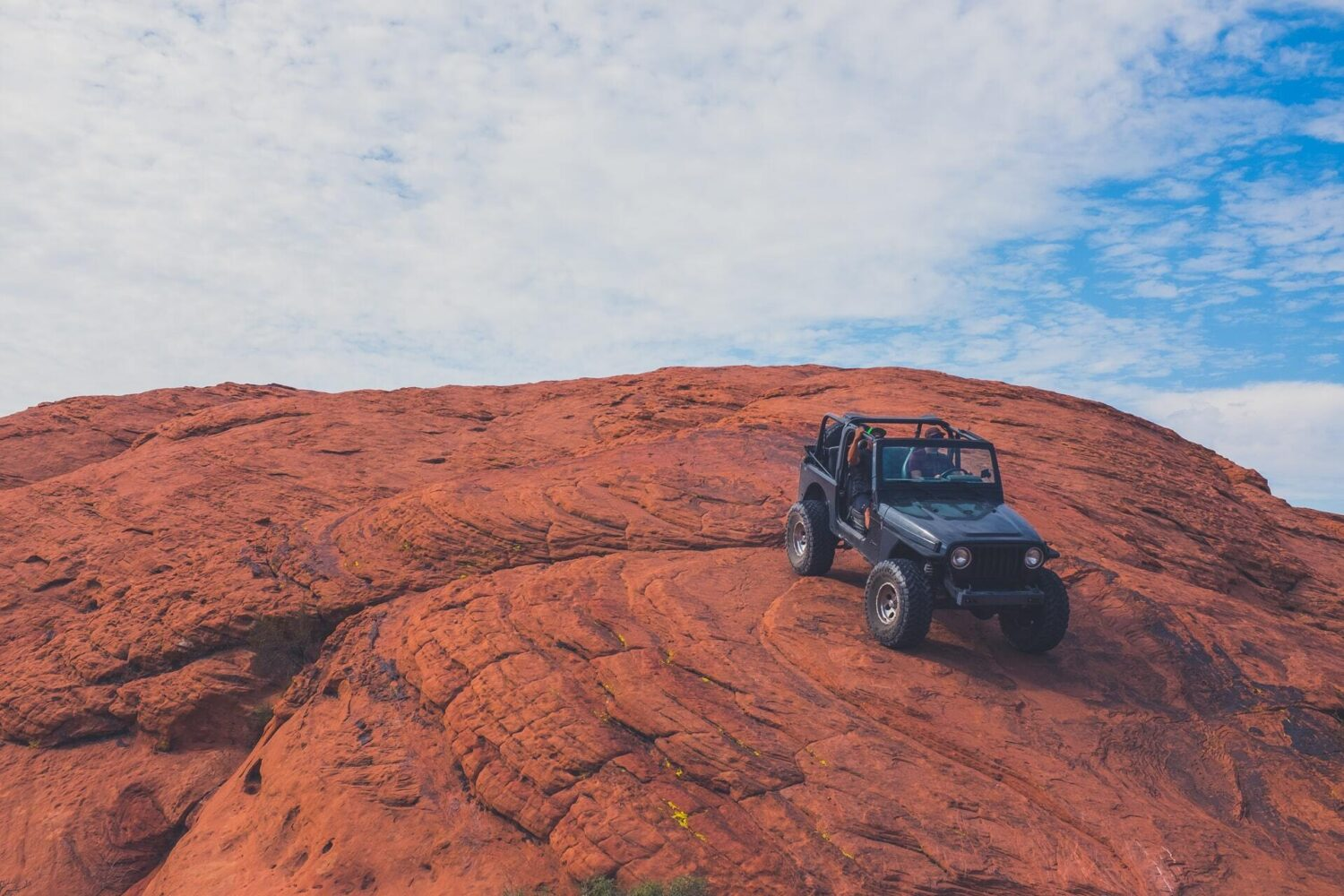 A jeep parked on a steep red rock with blue sky in the background