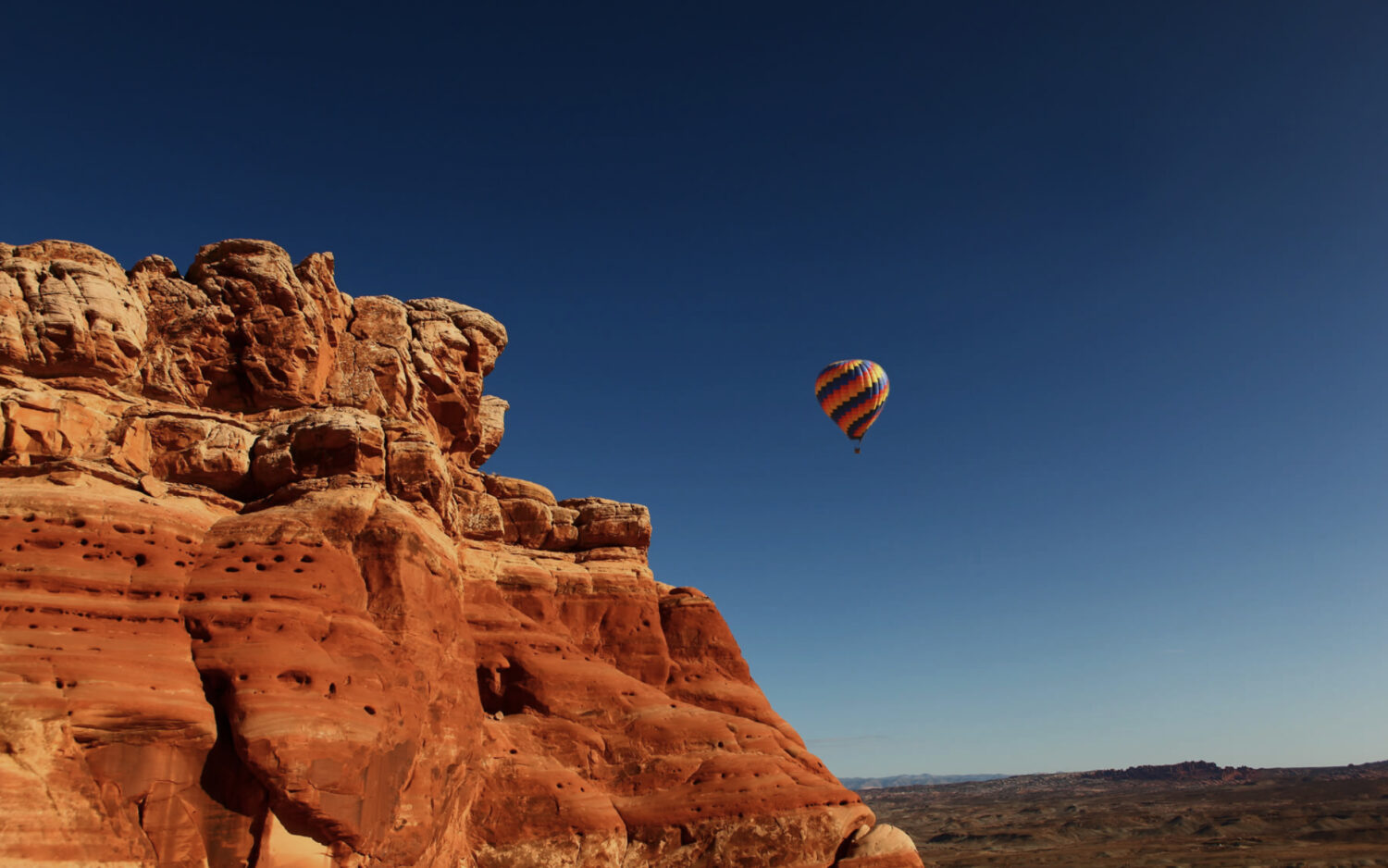 A hot air balloon floats past a high red cliff on a starry evening