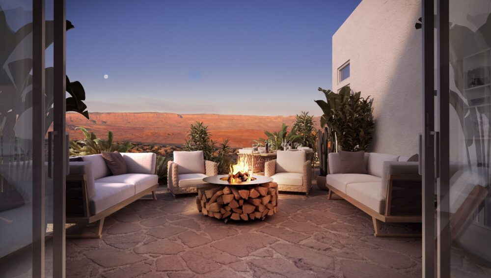 Private patio with firepit and comfy furniture at dusk, desert mountains in the distance